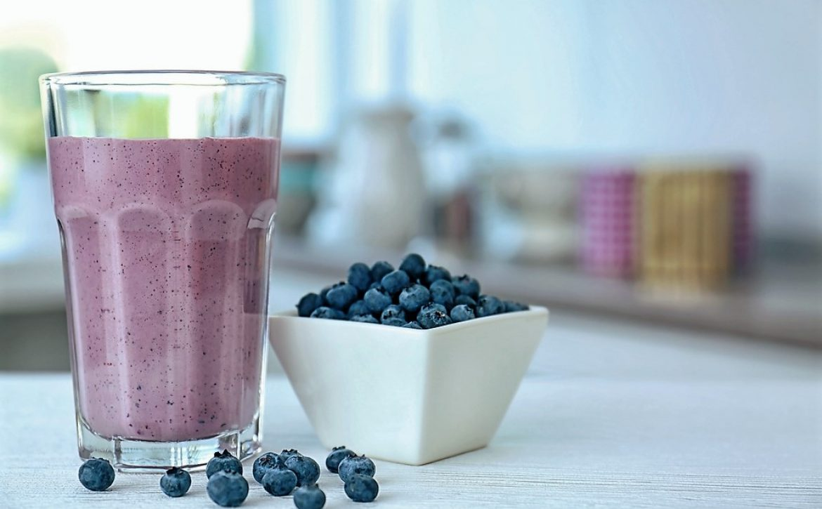 Glass with fresh blueberry smoothie and berries on kitchen table
